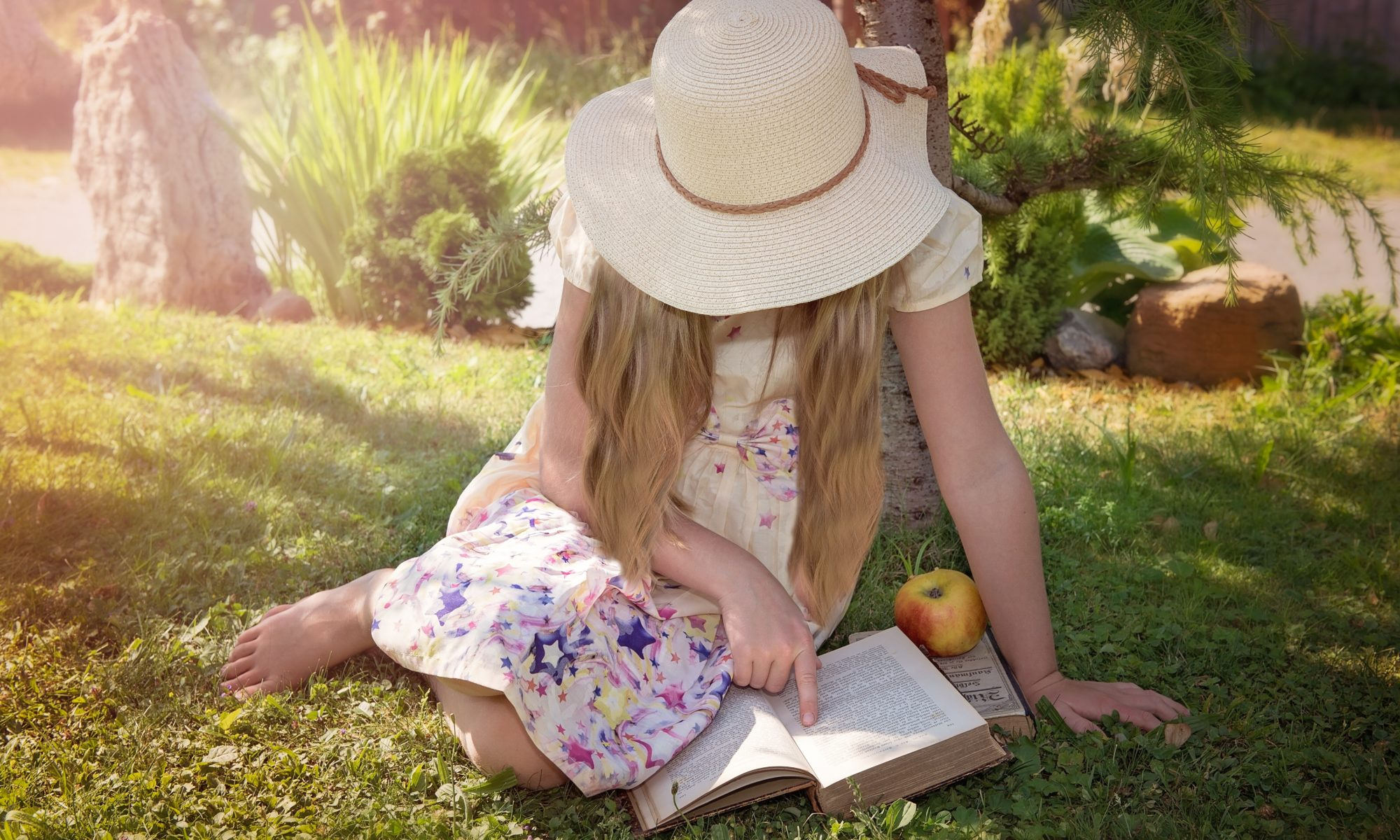 girl reading on the lawn with an apple next to her.
